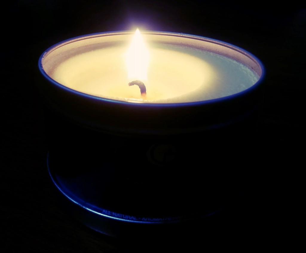 Candle with flame burning on short wick